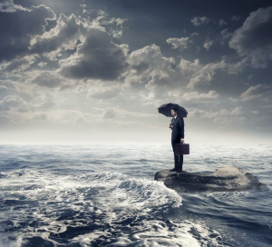 Resilience -- person on a small island surrounded by a stormy sea and rain holding an umberella