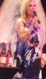 kathy lee with microphone and wine