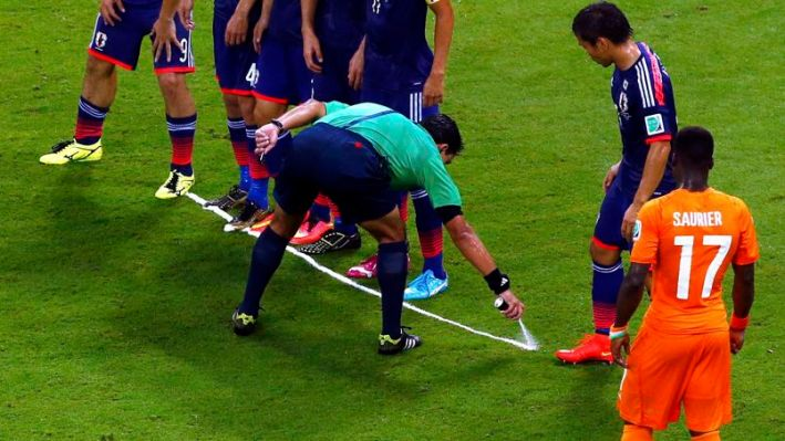 Referee Enrique Osses marks line during World Cup soccer match between Ivory Coast and Japan at Pernambuco arena