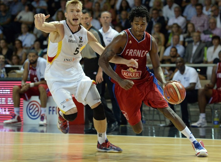 France's Mickael Gelabale (R) vies for the ball against Germany's Niels Giffey, during a friendly match between France and Germany, at the Rhenus hall in Strasbourg on August 28, 2015, ahead of the FIBA EuroBasket 2015 championship.  AFP PHOTO / PATRICK HERTZOG