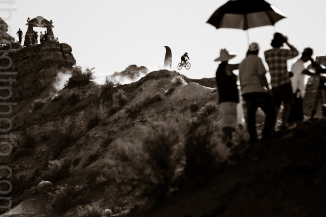 Videographers film a mountain biker as he rides the ridgeline at the Red Bull Rampage event in Utah.