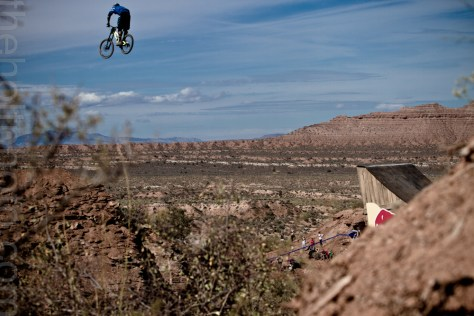 A mountain biker framed against the sky as he airs over the massive canyon gap at Red Bull Rampage.