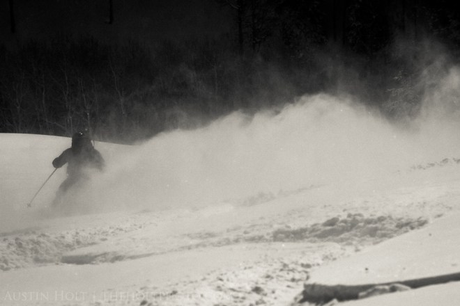 A backcountry skier leaving a trail of snow in the air as he makes a turn in powder snow in Utah.