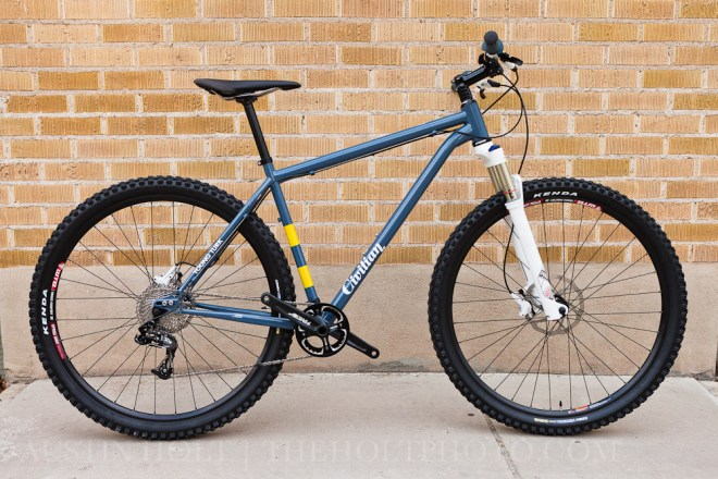 A complete Young Turk 29er mountain bike from Civilian Bikes photographed against a brick wall