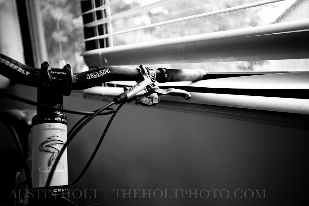 A bicycle's handlebars hold down the blinds over a window, giving the appearance that the bike is looking outside.