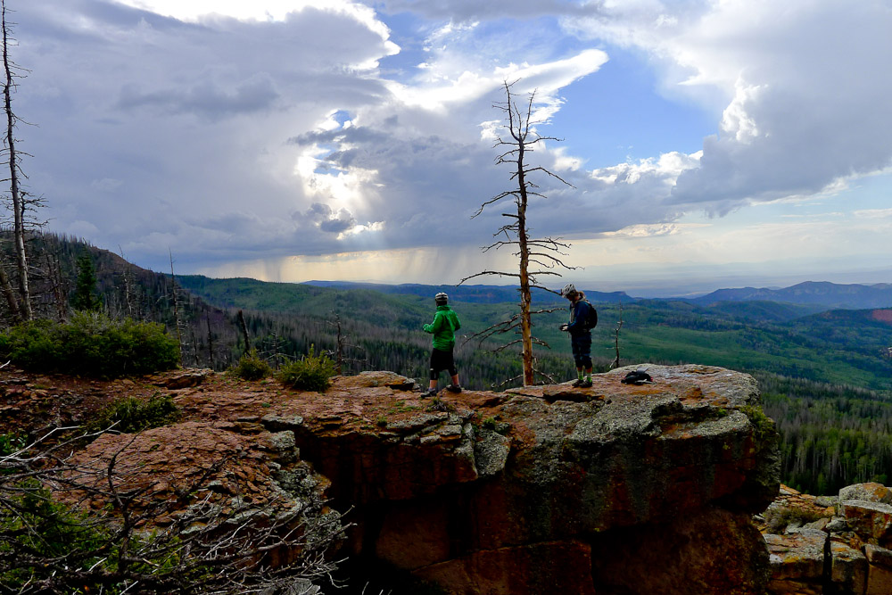 The sun peeks through a brewing storm cloud over Brian Head Utah. Two mountain bikers look on from a rocky cliff over the forest.