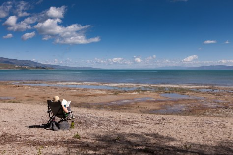 Re kicks back in a camp chair on the sunny shore of Bear Lake. Above her small clouds dot the bright blue sky.