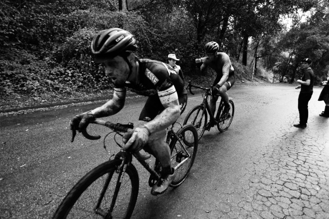 A black and white photo of two bike racers at the Surf City Cyclocross event in Aptos, California.