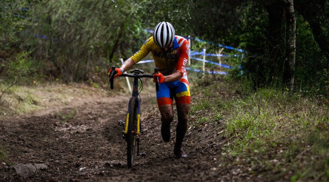 A cyclocross rider in a bright MASH kit runs up a muddy hill at the Surf City Cyclocross.