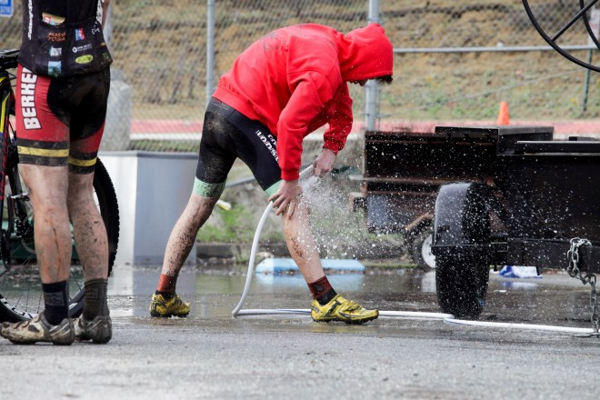 A muddy bike racer hoses off his legs after the All Hallow's Eve cyclocross race in Aptos, California.