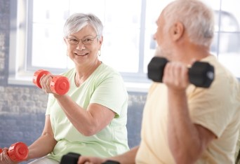 Vital senior couple exercising in the gym.