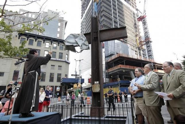 Father Brian Jordan (L), a Franciscan Priest, blesses The World Trade Center Cross, made of intersecting steel beams found in the rubble of buildings destroyed in the September 11 2001 attacks on the World Trade Center, before it is transported and lowered by a crane into an opening in the World Trade Center site below ground level where it will become part of the permanent installation exhibit in the 9/11 Memorial and Museum, in New York, July 23, 2011. REUTERS/Chip East