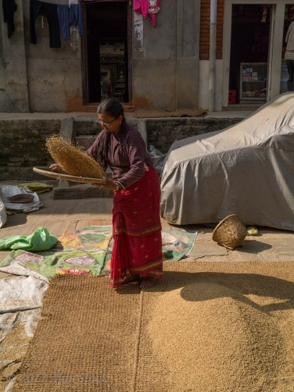 De-husking rice in the streets of Kiritipur