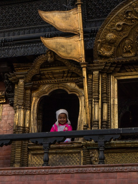 A girl spots us from a temple balcony near Durbar Square