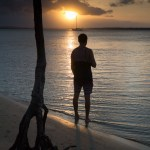 Silhouette Australia mangrove backpacker enjoys sunset view on beach