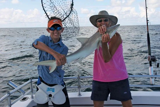 Shane Hogan is holding the tail and Capt. Judy Helmey (pink tank top) of Miss Judy Charters is holding the head of this shark, which was caught while using a  live black sea bass. As far as where did Shane hook up this fish? Right behind that shrimp boat!