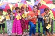 Actor Vijay Badlani distributes umbrellas to the needy children