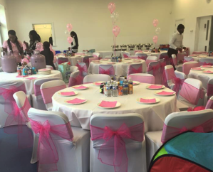 Room set up for wedding with pink bows and balloons