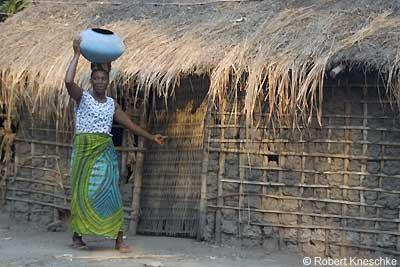 Frau vor Lehmhütte