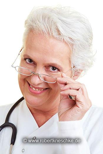 Ärztin schaut über ihre Brille
