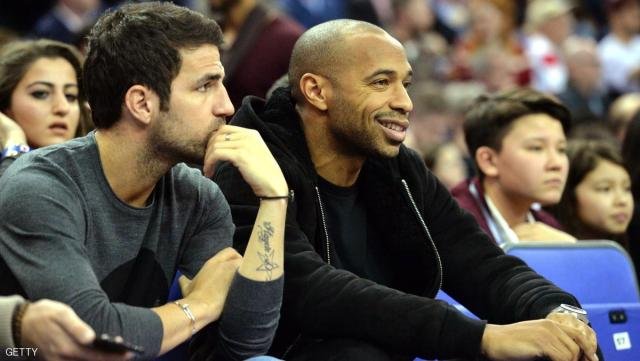 Chelsea footballer Cesc Fabregas (L) looks on as former footballer Thierry Henry (R) watch the 2015 NBA global game between Milwaukee Bucks and New York Knicks at the O2 Arena in London on January 15, 2015. AFP PHOTO / GLYN KIRK        (Photo credit should read GLYN KIRK/AFP/Getty Images)