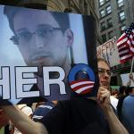 "A demonstrator holds a sign with a photograph of former U.S. spy agency NSA contractor Edward Snowden and the word ""HERO"" during Fourth of July Independence Day celebrations in Boston"