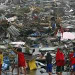 Survivors carrying their belongings walk past destroyed houses after Super Typhoon Haiyan battered Tacloban city in central Philippines