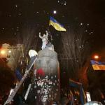 People climb up to the top of a pedestal after a statue of Soviet state founder Vladimir Lenin was toppled by protesters during a rally organized by supporters of EU integration in Kiev