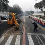 A traffic policeman guides a bulldozer removing the security barriers in front of the U.S. embassy in New Delhi
