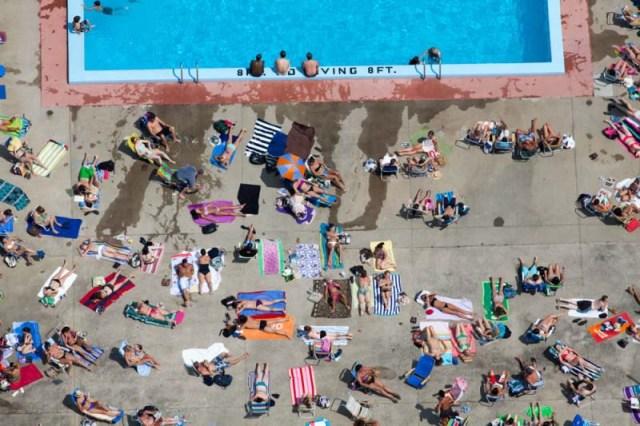 23. Pessoas tomam sol à beira de piscina