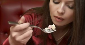 Beautiful brunette in red eats salad. Selective focus (mouth).