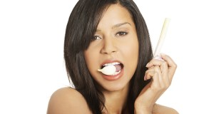 Young beautiful woman eating garlic. Natural antibiotic that fig