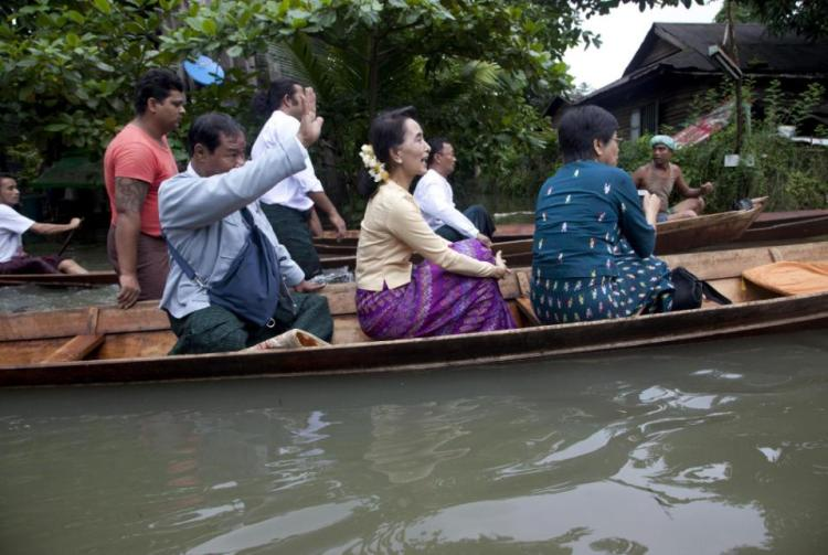 Myanmar opposition leader Aung San Suu Kyi, center, rides a boat on her way to a monastery where flood victims are sheltered, Monday, Aug. 3, 2015, in Bago, 80 kilometers (50 miles) northeast of Yangon, Myanmar. A report issued Saturday by the U.N. Office for the Coordination of Humanitarian Affairs cited Myanmar disaster officials estimating that more than 156,000 people had been affected by flooding. (AP Photo/Khin Maung Win)