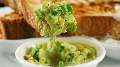 Delicious and colorful avocado dip with grilled Turkish bread.