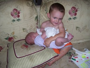 A toddler holds his newborn baby brother.