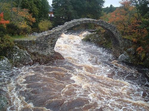 river rapids flowing under bridge