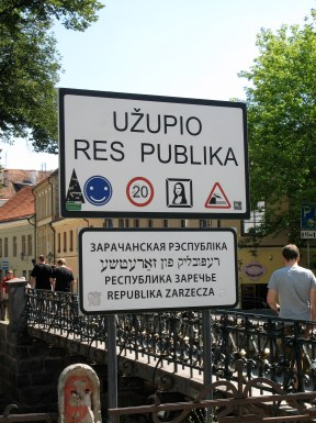 "description: a sign reading ""Uzupio Res Publika,"" with several translations including Yiddish."