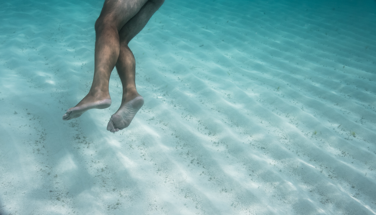 Artistic image of a mans legs swimming in turquoise water
