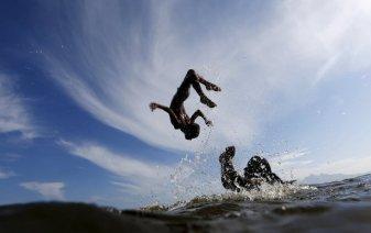 Dos niños saltan sobre el agua en las aguas de la playa Bica, en Río de Janeiro (Brasil) / Foto: Reuters