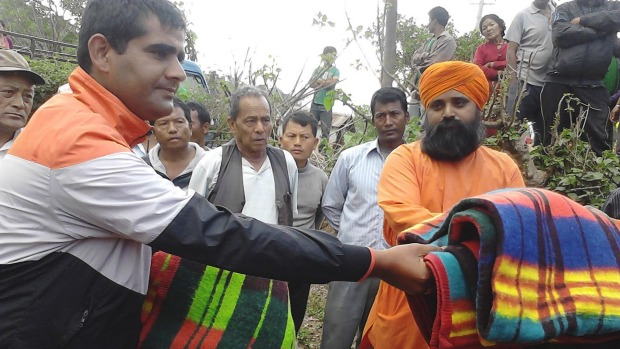 Ananda Marga volunteers distribute blankets at a relief camp in Nepal.