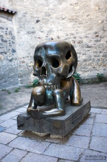 Скульптура бронзового человека, придавленного черепом. Расположена в тупике, в конце Златой улочки.