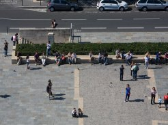 Люди отдыхают на площади перед Нотр-Дамом.