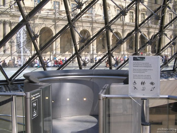 Кабина футуристического лифта внутри пирамиды в Лувре.