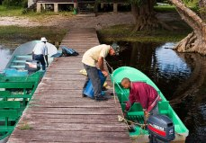 Жители деревни готовят лодку к экскурсии по заповеднику Crooked Tree.