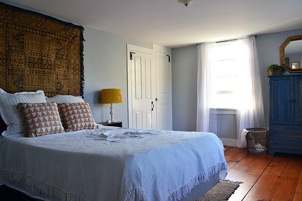 Guest bedroom with tapestry hanging behind the bed