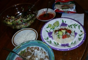 The makings of a vegan taco dinner:  clockwise from upper left,  finely chopped salad,  tortillas,  salsa,  a taco ready to roll,  a plate of refried beans and Crumbles,  and soy cheese.