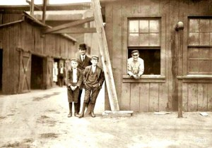"""These boys work off and on in the Cumberland Glass Works, Bridgeton, N.J. Smallest boy is George Cartwright, 401 N. Laurel Street. He says he has been working off and on since 11 years old."" Photo by Lewis Hine, November 1909. Note the black stable hand in the background."