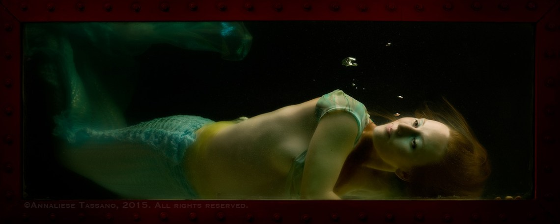 A pale, blond mermaid rests on the floor of the shadowy tank in which she is imprisoned.