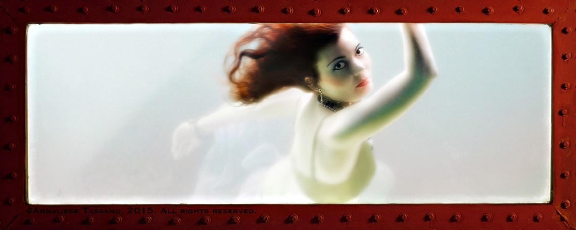 A redheaded mermaid looks out the window of her tank of glowing water.