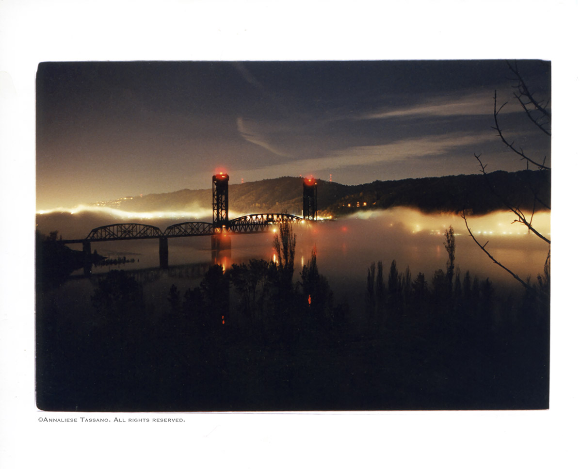 The St. Johns train bridge crossing the Willamette River in Portland, Oregon, red lights glowing and the west hills visible on the other side is seen on a foggy night.